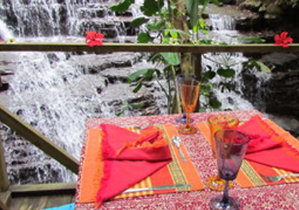 A table placed for a romantic lunch next to a waterfall