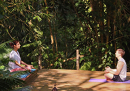 Two people practicing yoga surrounded by beautiful nature preserves.